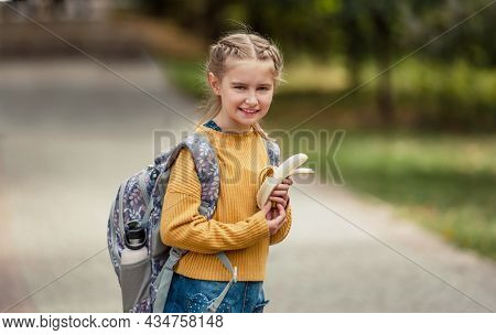 Preteen school girl with backpack holding bananas in her hands, looking at camera and smiling. Pretty pupil female kid after education class