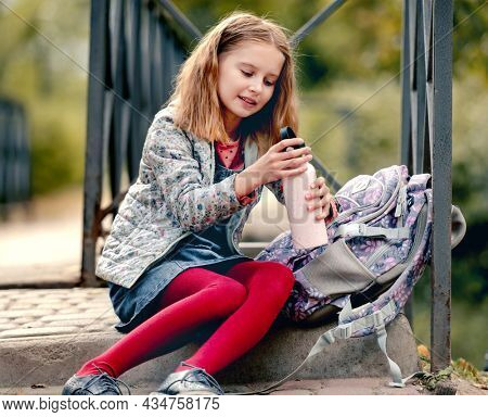 Preteen school girl with backpack sitting on ground and holding bottle with water. Sweet pupil female kid resting after education class in autumn park