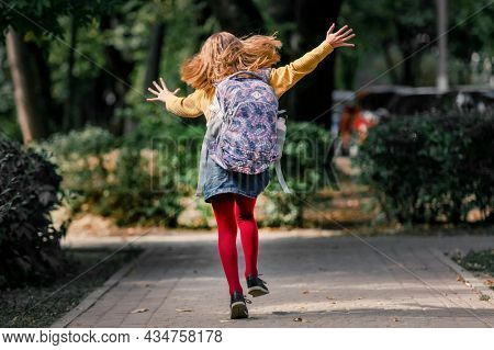 Preteen school girl with backpack running after class, back view. Pretty pupil female kid in autumn park
