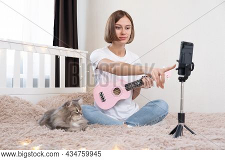 The Girl Leads A Video Blog About Playing The Ukulele. A Young Woman Blogger Sits On A Bed With A Ca