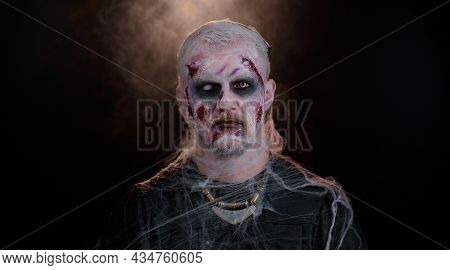 Sinister Man With Horrible Scary Halloween Zombie Makeup In Costume Making Faces, Looking Ominous At