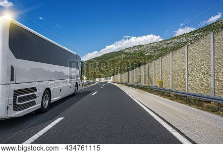 White Passenger Bus On The Highway Against The Backdrop Of A Beautiful Landscape.
