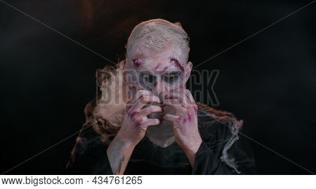 Sinister Man With Horrible Scary Halloween Zombie Makeup In Costume Blows Smoke From Nose And Mouth,