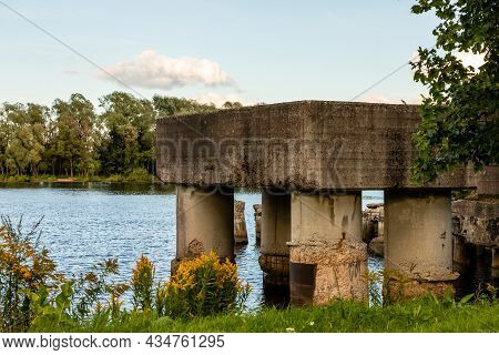 Lucavsala Stone Bridge Pillars Ruins In River Water During Sunny Summer Day. Scenic Photo Of Pier Re