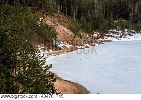 Frozen Lake And Brown Coast Covered With Pine Trees And Birches. Ice Covered Dubkalni Reservoir At Z