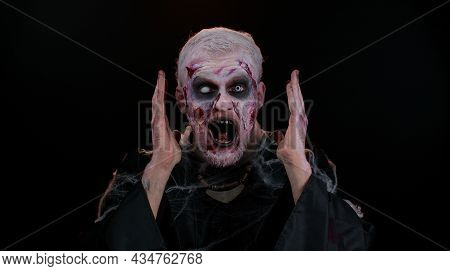Oh My God Wow. Frightening Man With Halloween Zombie Bloody Wounded Makeup Raising Hands In Surprise
