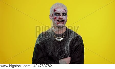 Cheerful Happy Creepy Man With Bloody Scars Face, Halloween Stylish Zombie Make-up. Scary Wounded Un