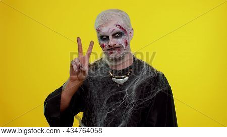 Frightening Man With Halloween Zombie Bloody Wounded Makeup Showing Victory Sign, Hoping For Success