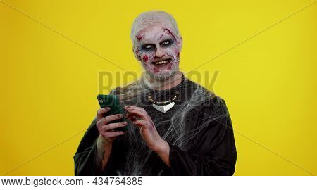 Frightening Man With Halloween Zombie Bloody Wounded Makeup Using Mobile Phone Typing New Post On We