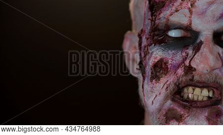 Close-up Macro Frightening Man Face With Halloween Zombie Blood Flows And Drips On Face, Trying To S