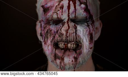 Close-up Of Sinister Man With Horrible Scary Halloween Zombie Makeup Making Faces, Looking Ominous A