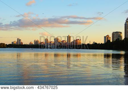 Amazing Autumn Landscape During Sunset. Buildings Reflected In The Tranquil Water Of The Dnieper Riv
