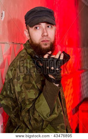 Young Bearded Terrorist With A Gun In The Stroma Of A Dilapidated Shelter