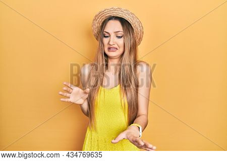 Young blonde girl wearing summer hat disgusted expression, displeased and fearful doing disgust face because aversion reaction.