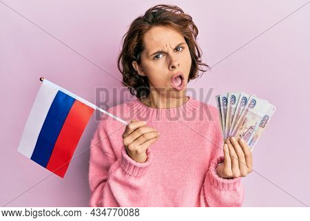 Young brunette woman holding russia flag and rubles banknotes in shock face, looking skeptical and sarcastic, surprised with open mouth