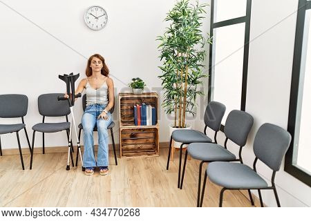 Young caucasian injuried girl with serious exrpression using crutches sitting at doctor waiting room.