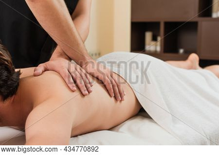 Cropped View Of Masseur Doing Massage To Man In Towel In Spa Center