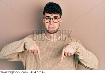 Young hispanic man wearing casual clothes and glasses pointing down looking sad and upset, indicating direction with fingers, unhappy and depressed.