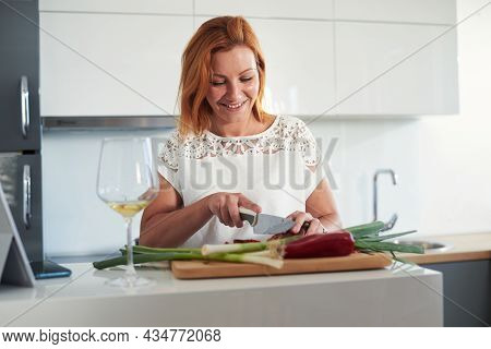 Woman portrait relaxing at home.Woman relaxing with wine at home. Domestic lifestyle. Woman portrait at home. Lifestyle. Happy woman portrait people at home. Relaxed people. Young people. Portrait of woman having wine with friends at home