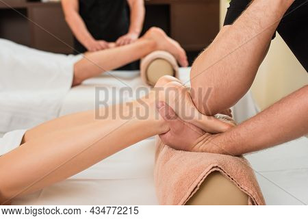 Cropped View Of Masseur Doing Feet Massage To Woman On Roller In Spa Center