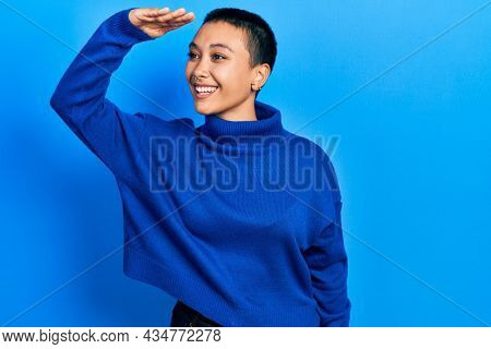 Beautiful hispanic woman with short hair wearing turtleneck sweater very happy and smiling looking far away with hand over head. searching concept.