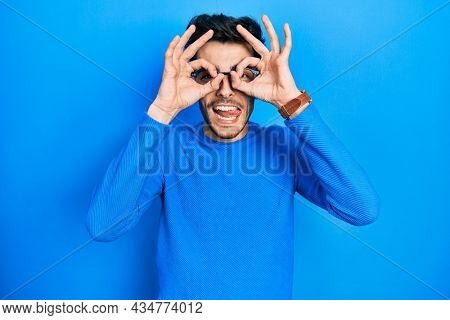 Young hispanic man wearing casual clothes and glasses doing ok gesture like binoculars sticking tongue out, eyes looking through fingers. crazy expression.