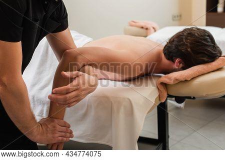 Masseur Doing Arm Massage To Client On Massage Table