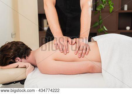 Masseur Doing Back Massage Of Man On Massage Table