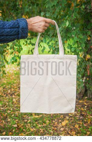 Stylish Man Hand Holding White Blank Canvas Tote Shopping Bag