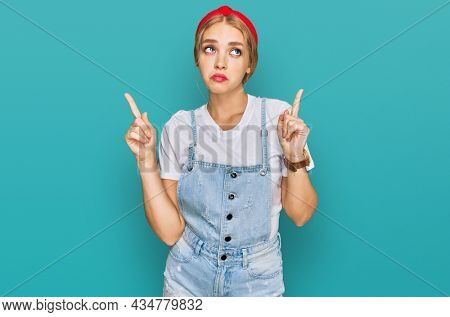 Young caucasian girl wearing casual clothes pointing up looking sad and upset, indicating direction with fingers, unhappy and depressed.
