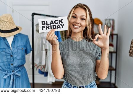 Young caucasian woman holding black friday banner at retail shop doing ok sign with fingers, smiling friendly gesturing excellent symbol
