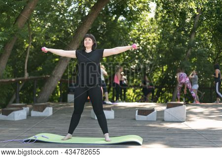 Young Girl Trainer Shows How To Do Hand Exercises With Dumbbells Outdoors In The Park. Circular Rota