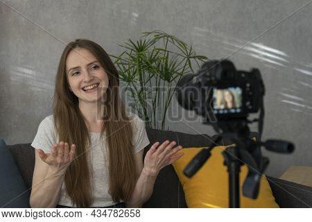 Beautiful Smiling Girl Is Filming Herself For A Video Blog. Young Blogger Filming Himself On Camera.