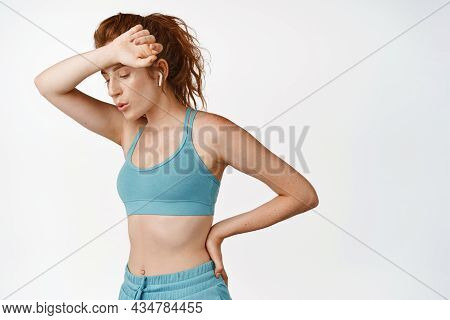 Young Redhead Sportswoman Wipe Sweat While Workout, Tired While Doing Fitness Exercises Or Jogging,