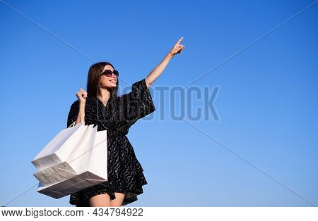 Beautiful Glamour Brunette Girl In Black Dress And Sunglasses Rejoices In Shopping Against The Blue