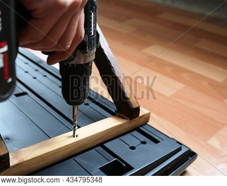 Assembling A Wooden Stand For A Synthesizer, Screwing A Screw Into A Wooden Strip Of A Shelf For A M