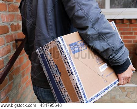 Maykop, Republic Of Adygea, Russia - October 1, 2021: A Postman With A Parcel Under His Arm Coming T