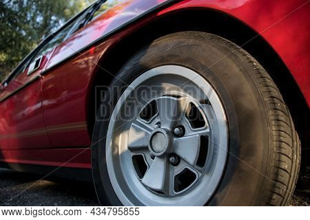 Closeup Partial View Of Red Sports Car With Alloy Rim And Tyre