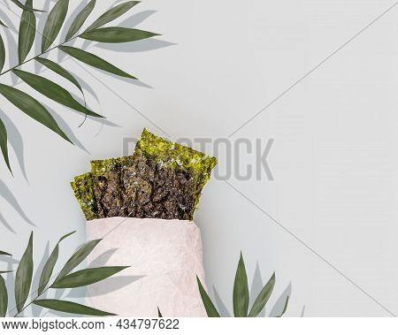 Salty Dried Seaweed Snack In A White Paper Bag With Palm Leaves On A Blue Background With Copy Space