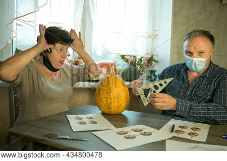 A Middle Aged Man And Woman Are Doing Jack O'lantern In The Kitchen. There Are Medical Masks On Peop