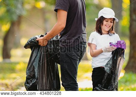 Picture Of A Smiling Beautiful Girl In Protective Gloves And Adult Man Volunteer Gathering Plastic R