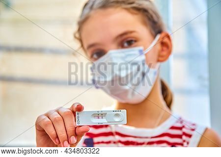 Girl In White Medical Mask Holds The Fast And Simple Self-test The Covid-19 Antigen With Positive Re