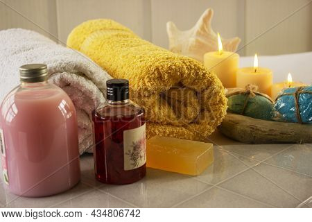 The Bathroom Accessories And Cosmetic Products. Three Terry Towels In A Wicker Basket, Body Lotion,