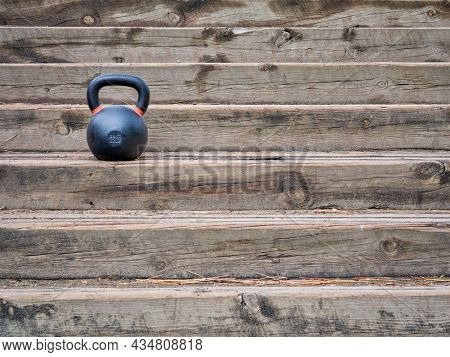 heavy iron competition kettlebell for weight training on rustic wooden stairs, outdoor fitness concept
