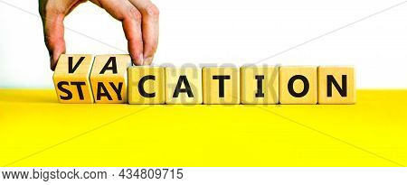 Vacation Or Staycation Symbol. Businessman Turns Wooden Cubes And Changes The Word Vacation To Stayc