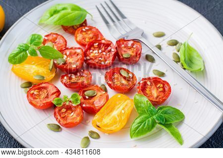 Sun-dried Tomatoes With Basil, Sesame Seeds And Pumpkin On A Plate On A Black Background. Vegetarian