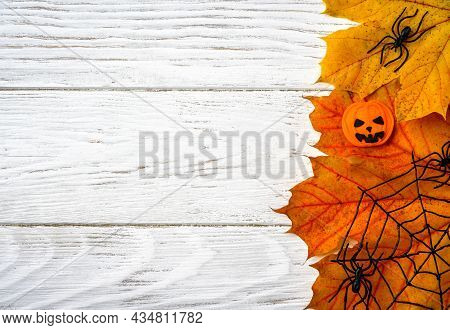 Halloween Background With Fall Maple Leaves, Top View. Halloween Objects On White Wooden Table With