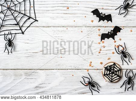 Halloween Background With Cookie, Spiders And Bats, Top View. Halloween Objects On White Wooden Tabl
