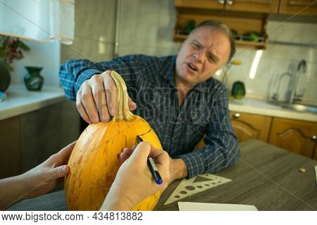 Making Jack O\'lantern At Home. The Process Of Creating A Jack O\'lantern Theme Template. A Man And