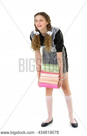 Tired Pretty Girl Carrying Pile Of Heavy Books. Graduate Teenage Girl With Braided Hair Wearing Blac